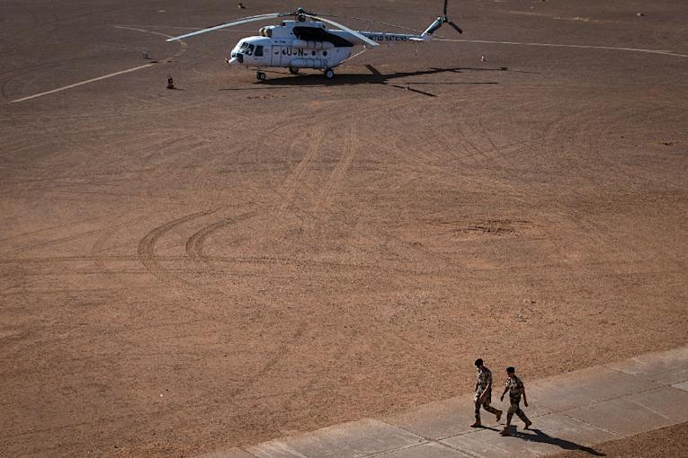 Soldiers walk near an United Nations helicopter on December 31, 2013 at a military base in Gao, northern Mali (AFP Photo/Joel Saget)