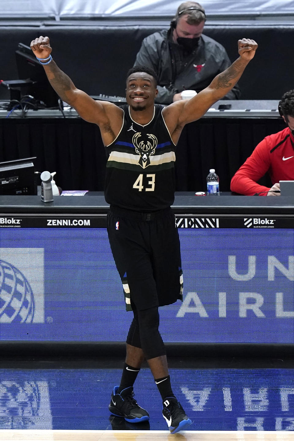 Milwaukee Bucks forward Thanasis Antetokounmpo looks up the score board as celebrates after guard Elijah Bryant scored a basket during the first half of an NBA basketball game against the Chicago Bulls in Chicago, Sunday, May 16, 2021. (AP Photo/Nam Y. Huh)