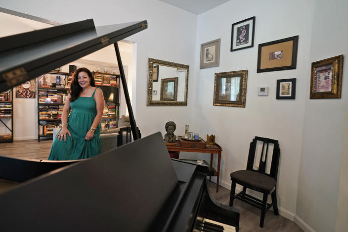 Heather Bise, owner of The House of Bise Bespoke, poses in the library, Monday, July 19, 2021, in Cleveland. Small businesses in the U.S. that depend on tourism and vacationers say business is bouncing back, as people re-book postponed trips and take advantage of loosening restrictions, a positive sign for the businesses that have struggled for more than a year. Bise started in 2019 and catered to international tourists, attracting guests from New Zealand, Botswana, Eastern Europe and elsewhere. (AP Photo/Tony Dejak)