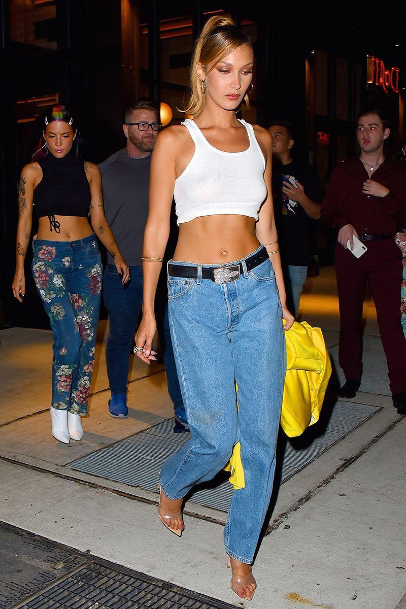 <p>In a white tank top, blue jeans, a black belt, clear pointed heels, gold hoops, and gold bracelets.</p>