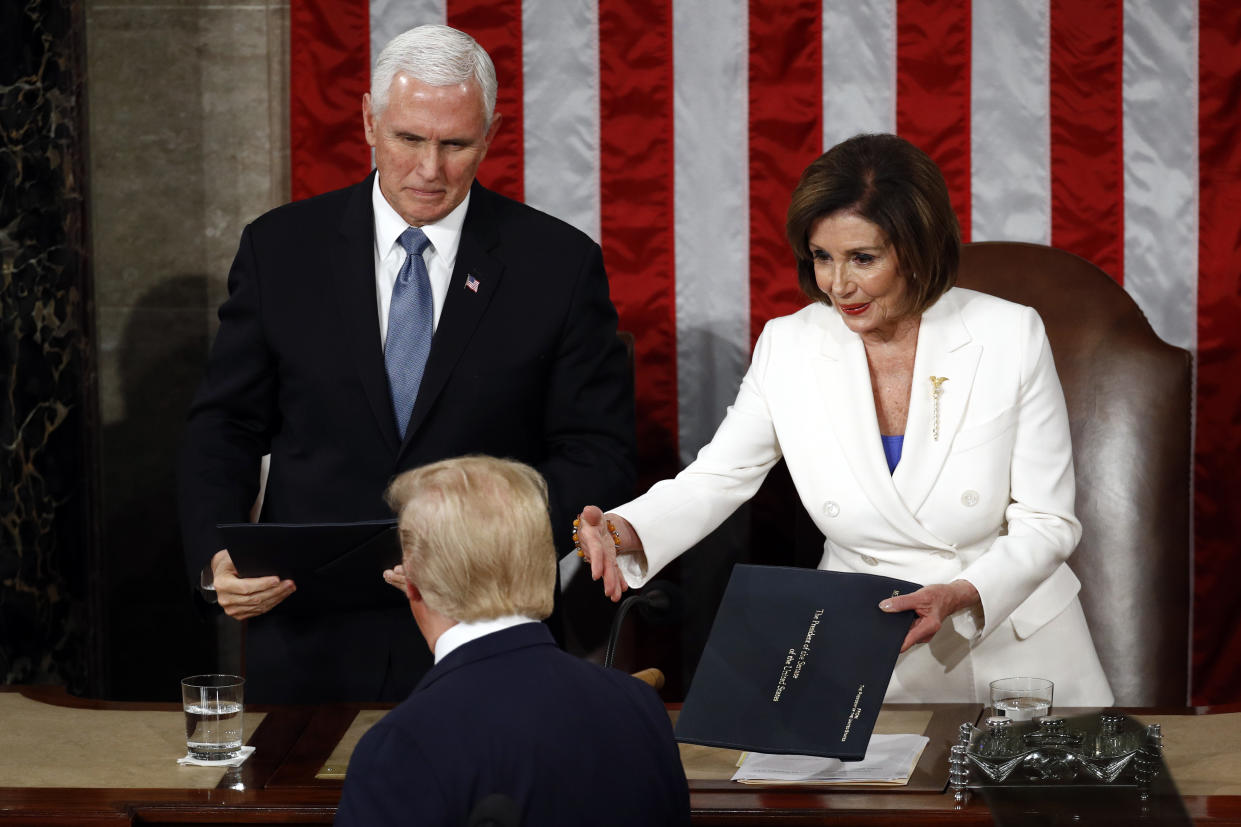 President Donald Trump hands copies of his speech to House Speaker Nancy Pelosi of Calif., and Vice President Mike Pence as he delivers his State of the Union address to a joint session of Congress on Capitol Hill in Washington, Tuesday, Feb. 4, 2020. (Patrick Semansky/AP)