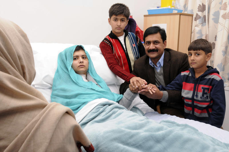 FILE - In this undated file handout photo issued by Queen Elizabeth Hospital, Malala Yousufzai, at left in her hospital bed, poses for a photograph with her father Ziauddin, second right accompanied by her two younger brothers Atal, right and Khushal, in Birmingham, England. The mtvU network is honoring, Yousufzai who was shot for her education advocacy, as its Woman of the Year. (AP Photo/ Queen Elizabeth Hospital Birmingham)