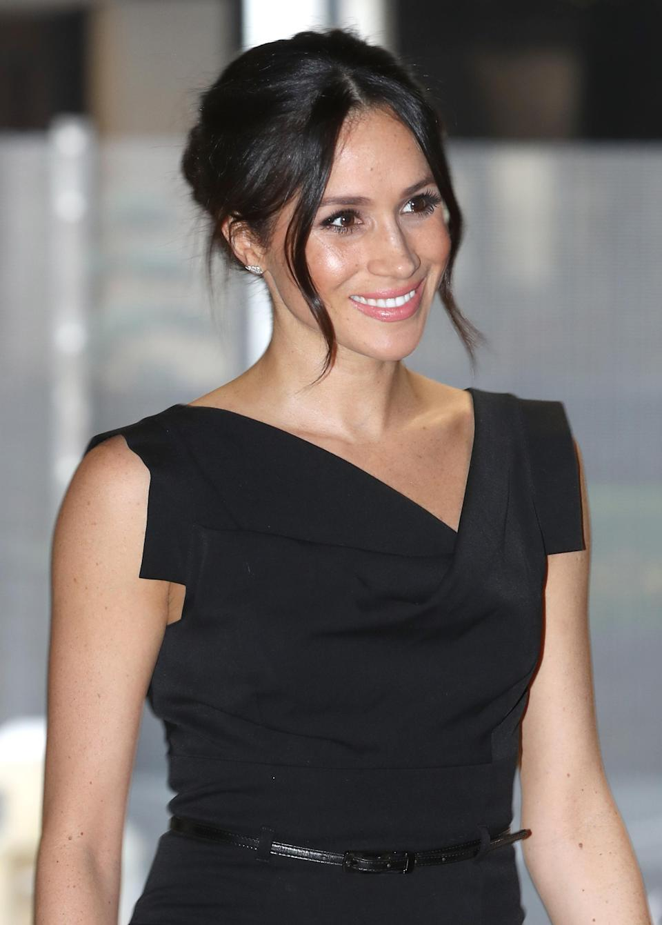 <p>Markle dazzled the cowl neck belted cocktail dress and diamond earrings from Birks. </p>