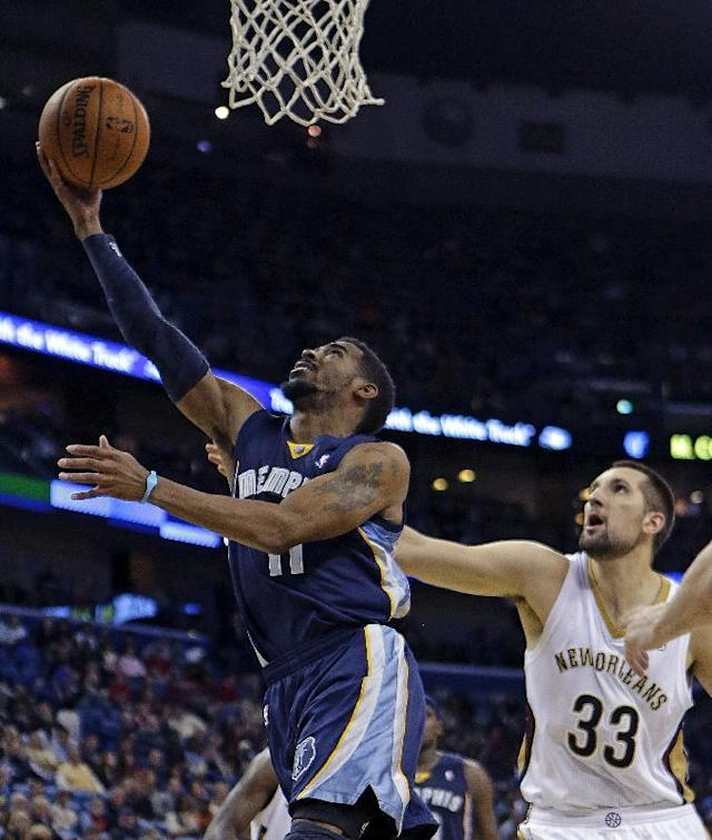 Memphis Grizzlies point guard Mike Conley (11) drives to the basket in front of New Orleans Pelicans power forward Ryan Anderson (33) in the first half of an NBA basketball game in New Orleans, Friday, Dec. 13, 2013. (AP Photo/Gerald Herbert)