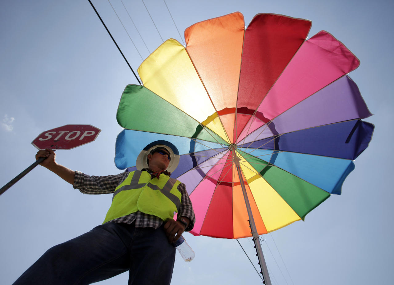 Alan Perez, from Wilmington, N.C., seeks shelter from the sun under an umbrella while holding a stop sign to close a road for debris removal Tuesday, July 19, 2011 in Joplin, Mo. Despite a recent heat wave, crews continue to clean up nearly two months after an EF-5 tornado destroyed much of Joplin. (AP Photo/Charlie Riedel)