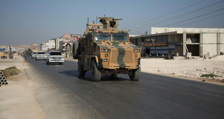 A Turkish army convoy drives past the Bab al-Hawa crossing with Syria on August 24, 2019 on its way to reinforce a Turkish military observation point in northwestern Syria (AFP Photo/Aaref WATAD)