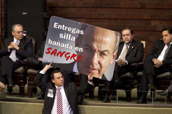 """A member of Mexico's National Congress holds a poster with an image of outgoing President Felipe Calderon that reads in Spanish: """"You are giving a chair bathed in blood,"""" prior to the inauguration ceremony of incoming President Enrique Pena Nieto in Mexico City, Saturday, Dec. 1, 2012. Pena Nieto took the oath of office as Mexico's new president on Saturday, bringing the old ruling party back to power after a 12-year hiatus amid protests inside and outside the congressional chamber where he swore to protect the constitution and laws of the land. (AP Photo/Alexandre Meneghini)"""