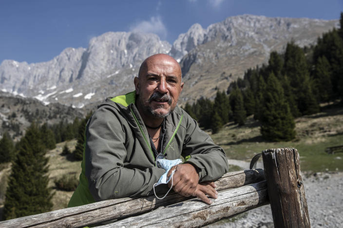 """In this image take on Friday, April 24, 2020 Claudio Trentani, 57, poses for a portrait outside the shelter 'Baita Cassinelli', at 1568mt, at the foot of Mt. Presolana, seen in the background, in Castione della Presolana, near Bergamo, northern Italy. On Saturday, March 7, 2020, a day before the national lockdown was announced, he had over 100 people for lunch and was sincerely worried about the risks of infection. Now he is waiting to see if he can reopen under new laws applicable to restaurants, but with his indoor area of about 60 mq he is hoping to make the most of his outdoor space. """"It is a powerful tragedy that has touched chords that not even during the war had been touched."""" (AP Photo/Luca Bruno),"""