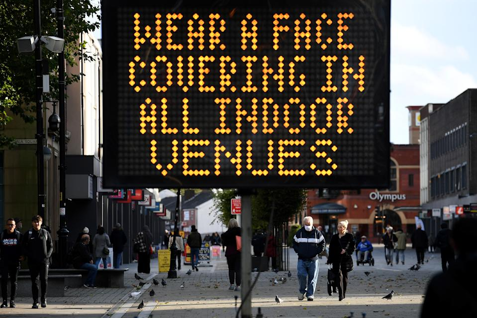 Pedestrians walk past an electronic road sign displaying COVID-19 information advising the use of face coverings for all indoor venues, in Bolton town centre, northwest England on October 7, 2020. - The UK government recently imposed tougher coronavirus restrictions in northwest England, as it voiced fears about rising infection rates among younger people. (Photo by Oli SCARFF / AFP) (Photo by OLI SCARFF/AFP via Getty Images)