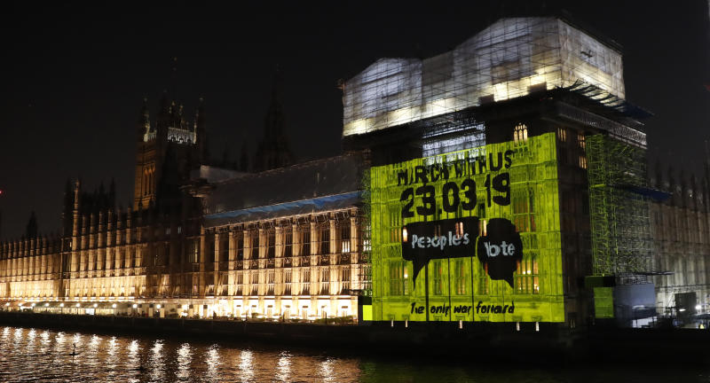 """A projection calling for a second referendum or a so-called """"Peoples's vote"""", is cast onto the Houses of Parliament in London, Wednesday Feb. 27, 2019. British Prime Minister Theresa May says she will give British lawmakers a choice of approving her divorce agreement, leaving the EU March 29 without a deal or asking to delay Brexit by up to three months. (AP Photo/Alastair Grant)"""