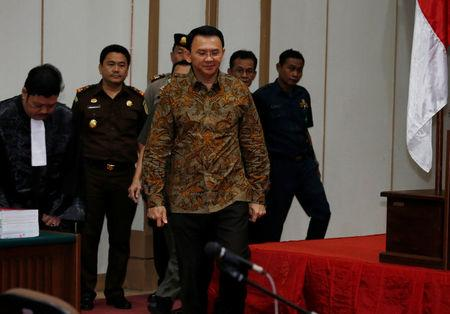 Jakarta's Governor Basuki Tjahaja Purnama, also known as Ahok, walks inside the courtroom as arrives for his blasphemy trial at the auditorium of the Agriculture Ministry, in Jakarta