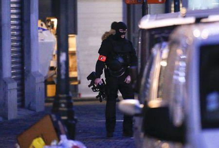 A Belgian special forces police officer patrols a street during a police raid in central Brussels, Belgium, in connection with last month's deadly Paris attack