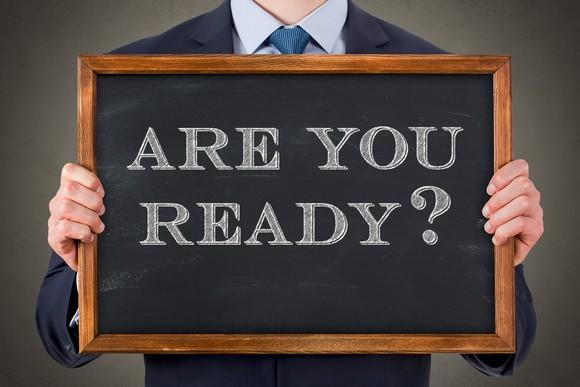 man in suit holding small chalkboard on which is printed are you ready?