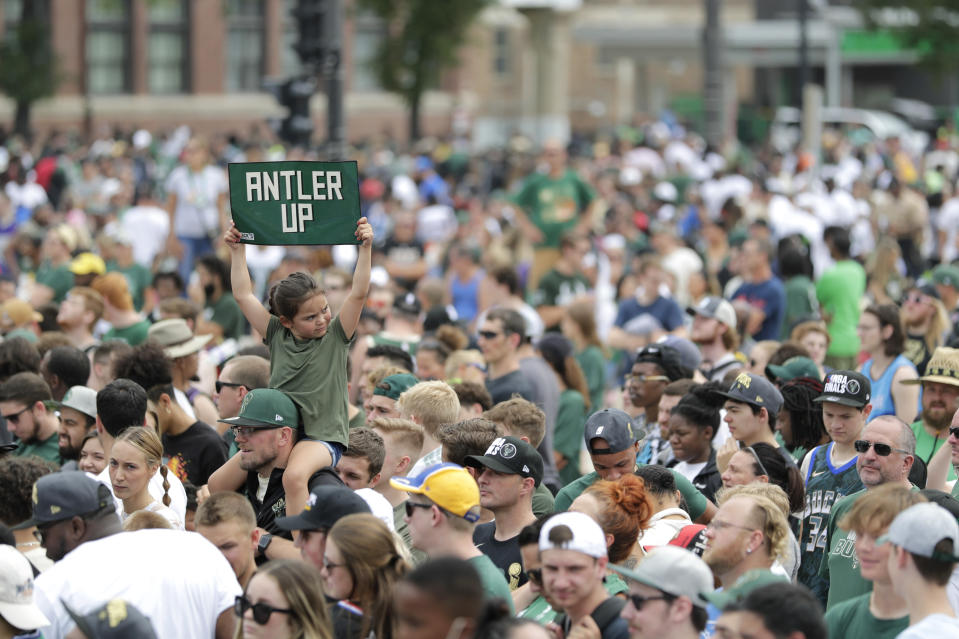 A fan holds up a sign during a parade celebrating the Milwaukee Bucks' NBA Championship basketball team Thursday, July 22, 2021, in Milwaukee. (AP Photo/Aaron Gash)