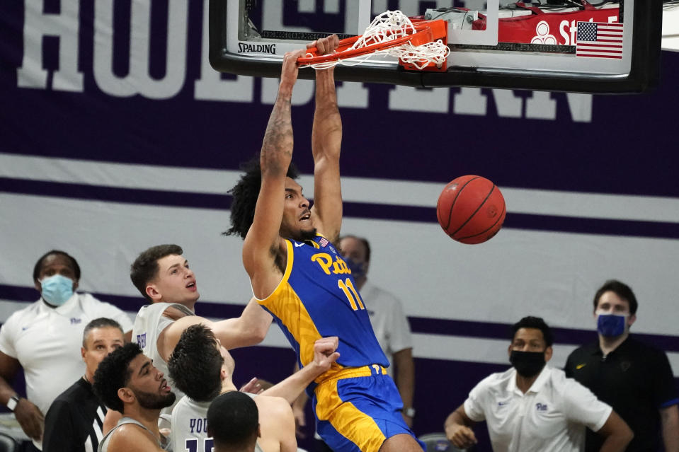 FILE - Pittsburgh's Justin Champagnie (11) dunks against Northwestern during the second half of an NCAA college basketball game in Evanston, Ill., in this Wednesday, Dec. 9, 2020, file photo. Champagnie is a member of The AP All-ACC first team, announced Tuesday, March 9, 2021. (AP Photo/Nam Y. Huh, File)