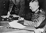 """<p>Wilhelm Keitel, Chief of Defense for Germany, signs the surrender terms for the German Army in Berlin. Keitel was tried in the Allied court at Nuremberg, sentenced to death, and hanged as a war criminal. His reported last words: """"I call on God Almighty to have mercy on the German people. More than two million German soldiers went to their death for the fatherland before me. I follow now my sons—all for Germany.""""</p>"""