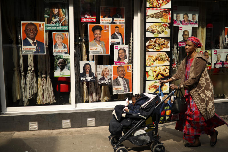 A woman walks past political campaign posters placed on a restaurant window at the African Matonge quarter in Brussels, Wednesday, May 22, 2019. Belgium, which has one of the oldest compulsory voting systems, will go to the polls for regional, federal and European elections on May 26, 2019. (AP Photo/Francisco Seco)