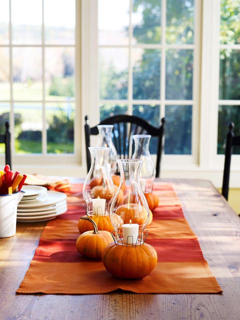 <p>Fill your fall dinner table with a festive display of white votives set on top of mini pumpkins. </p>