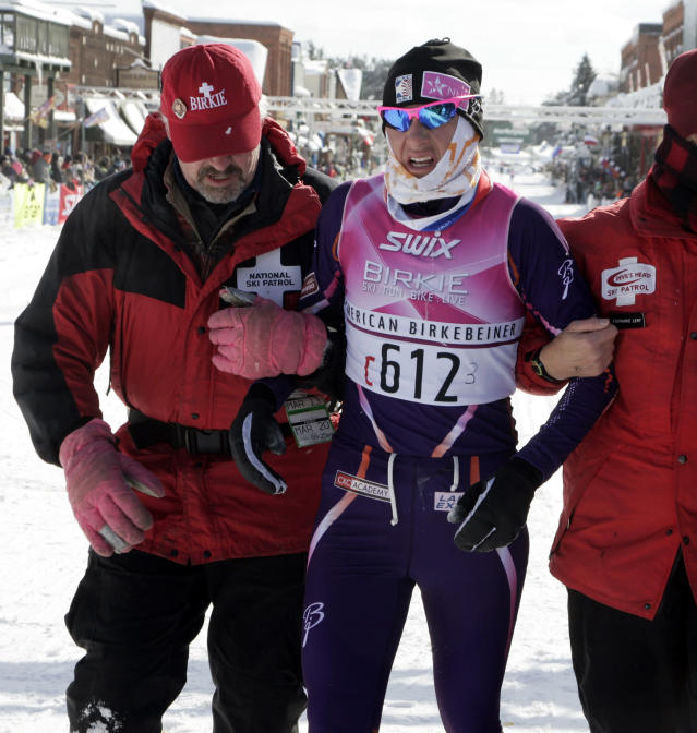 Natalja Naryshkina, of Cable, Wis., is helped after crossing the finish line at the American Birkebeiner, in the the 54k Birkie Classic race, in Hayward, Wis., on Saturday, Feb. 22, 2014. Naryshkina finished with a time of 3:26:00.6. (AP Photo/Paul M. Walsh)