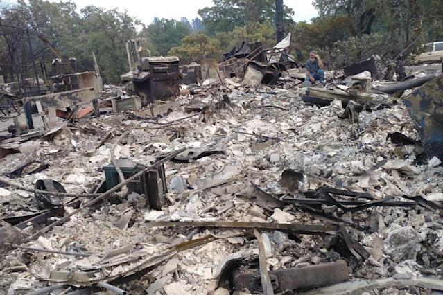 Jerry Ogle's father sits on the rubble that used to be his family's home. (Photo: GoFundMe)