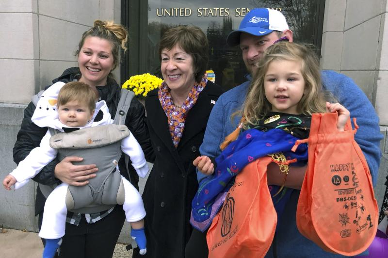 In this Friday, Oct. 25, 2019 photo, Sen. Susan Collins, R-Maine, poses with citizens for a photo outside her office during a tricks-or-treat event hosted by the local chamber of commerce in Lewiston, Maine. Collins is expected to make a formal announcement on her reelection plans later this fall. (AP Photo/David Sharp)