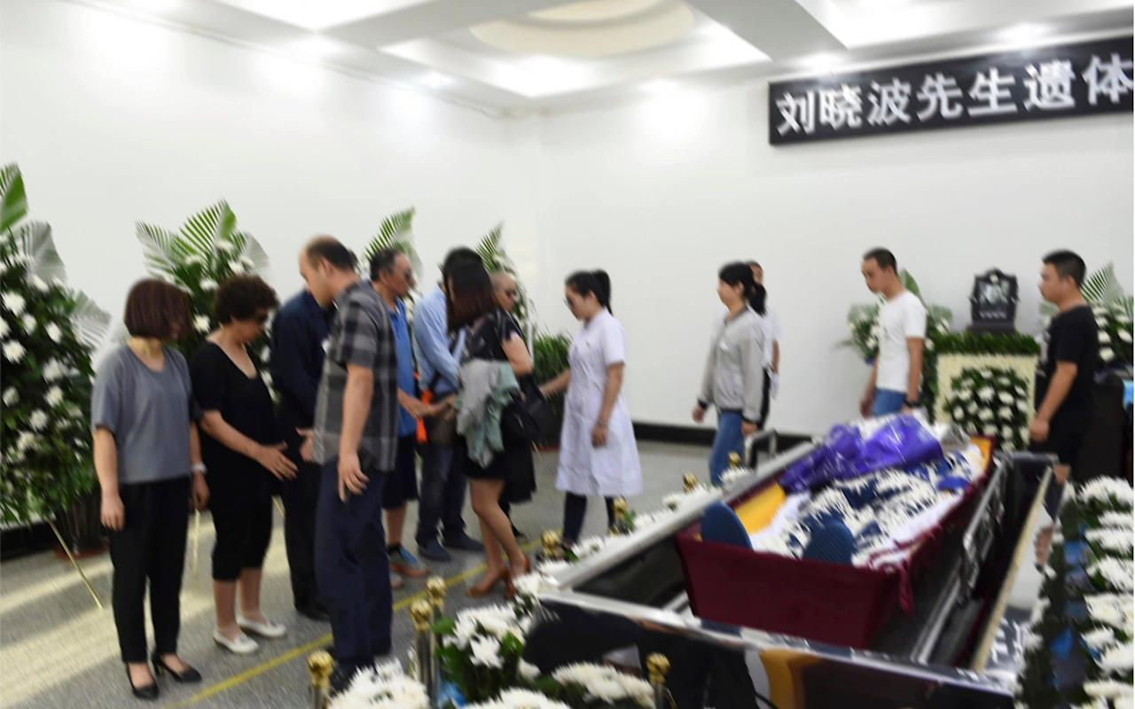 """The body of Liu Xiaobo, the Nobel laureate who died after years of imprisonment in China, was cremated Saturday after a private ceremony attended by his family and several men believed to be Chinese secret police. Liu's remains were incinerated """"in accordance with the will of his family members and local customs"""" in the northeastern city of Shenyang, said Zhang Qingyang, an official from the municipal office. His ashes were later scattered in the sea. Officials released photos showing his wife, the poet Liu Xia, with her brother, and two of Liu Xiaobo's brothers in front of the body, which was covered with white petals and surrounded by flowers at a funeral home. Zhang also said """"friends"""" were at the ceremony, but an Amnesty International researcher said he did not recognise any of the row of non-family members in the official photo and people close to the Liu couple identified at least one """"state security police officer"""" among them. The dissident's wife Liu Xia, centre, scattered his ashes into the sea Credit: EPA/SHENYANG MUNCIPAL INFORMATION OFFICE Chinese dissident artist critic Ai Weiwei, who lives in Berlin tweeted a photo of the funeral and called the display """"disgusting"""" and a """"violation"""" of the deceased. China's government faced a global backlash for denying the democracy advocate's wish to be treated abroad. After his death, the United States and European Union called on Beijing to free Liu Xia, who has been under house arrest since 2010, and let her leave the country. """"As far as I know, Liu Xia is in a free condition,"""" Zhang said, though it was unclear whether she was released as he did not answer questions about her whereabouts. Authorities have severely restricted Liu Xia's contact with the outside world and Jared Genser, a US lawyer who represented the Nobel Peace Prize winner, said she has been held """"incommunicado"""" since her husband's death. """"The most preposterous thing is that even during his cremation and funeral he still was not free. And now it's """