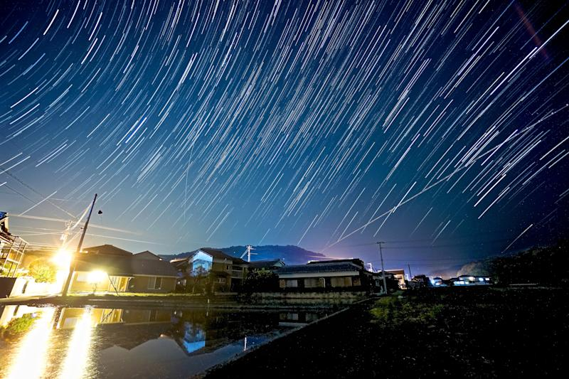 Star trails including a meteor trail over rice fields and houses in Kagawa Prefecture, Japan.