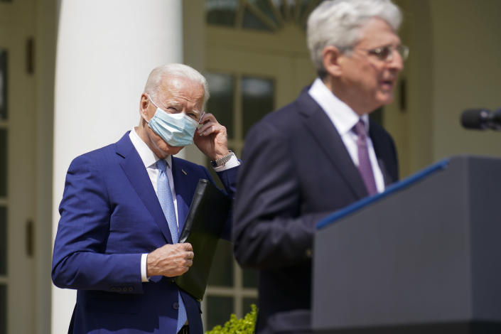President Joe Biden, adjusts his face mask as he listens to Attorney General Merrick Garland speak about gun violence prevention in the Rose Garden at the White House, Thursday, April 8, 2021, in Washington. (AP Photo/Andrew Harnik)