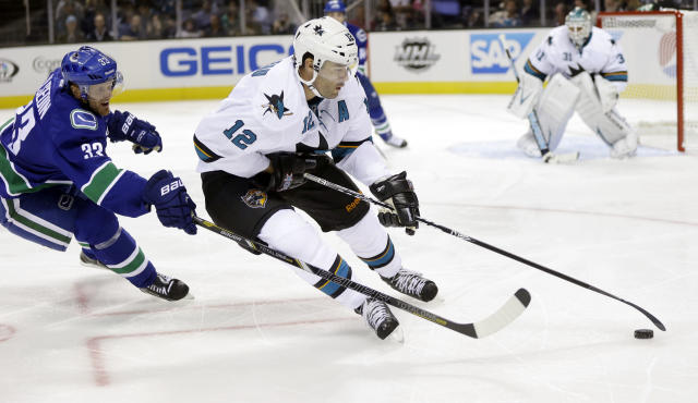 San Jose Sharks' Patrick Marleau (12) is chased by Vancouver Canucks' Henrik Sedin (33) during the second period of a preseason NHL hockey game on Tuesday, Sept. 24, 2013, in San Jose, Calif. (AP Photo/Marcio Jose Sanchez)