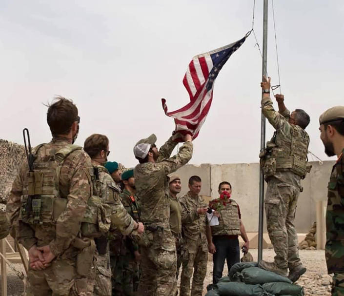 FILE - In this May 2, 2021 file photo, a U.S. flag is lowered as American and Afghan soldiers attend a handover ceremony from the U.S. Army to the Afghan National Army, at Camp Anthonic, in Helmand province, southern Afghanistan. The US and NATO have promised to pay $4 billion a year until 2024 to finance Afghanistan's military and security forces, which are struggling to contain an advancing Taliban. Already since 2001, the U.S. has spent nearly $89 billion to build, equip and train the forces. (Afghan Ministry of Defense Press Office via AP, File)