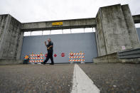 A Plaquemines Parish sheriff deputy walks away after workers closed a floodwall gate on Hwy 39 in Poydras, La., Wednesday, Oct. 28, 2020. Hurricane Zeta is expected to make landfall this afternoon as a category 2 storm. (AP Photo/Gerald Herbert)