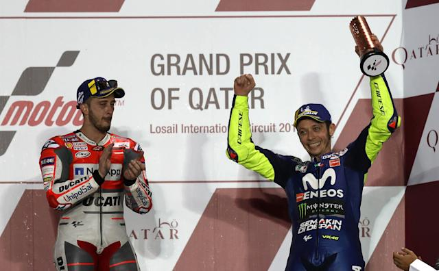 Motorcycle Racing - Qatar Motorcycle Grand Prix - MotoGP race - Losail, Qatar - March 18, 2018 - Third-placed Movistar Yamaha rider Valentino Rossi of Italy celebrates as first-placed Ducati Team rider Andrea Dovizioso of Italy claps. REUTERS/Ibraheem Al Omari