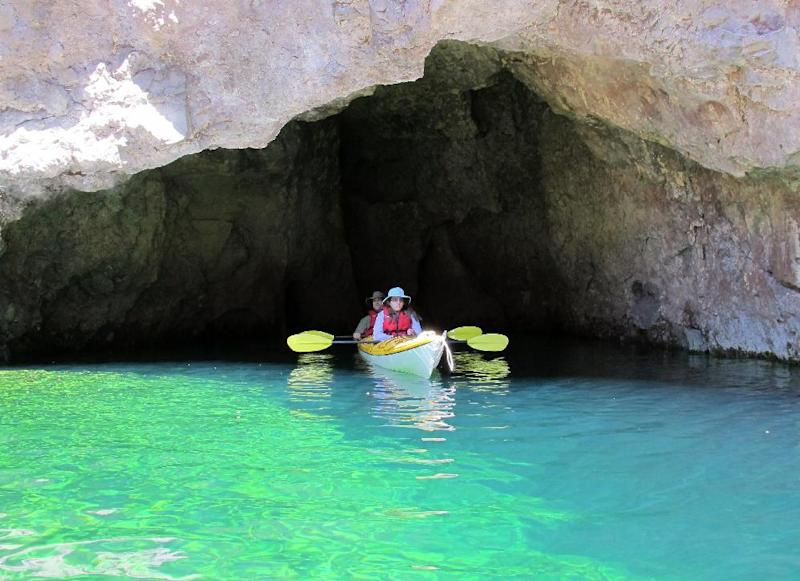 This April 14, 2013 photo shows kayakers at the Emerald Cave on the Arizona side of the Colorado River. The cave is one of the highlights of a trip on the river that begins with a guide company picking you up at a hotel on the Las Vegas Strip first thing in the morning, putting in near the Hoover Dam in a federal security zone that requires escort by an authorized livery service, and paddling through the Black Canyon. (AP Photo/Karen Schwartz)