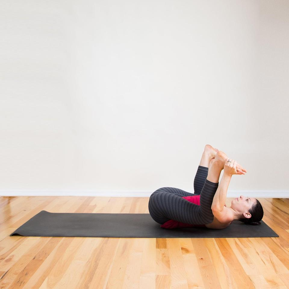 <ul> <li>Lying on the back, bend both knees, and hold the outside edges of your flexed feet with your hands. Keep your arms on the outsides of your legs.</li> <li>Gently use your upper-body strength to equally press both knees to the floor below your armpits. Try not to tense your shoulders or chest, but keep everything relaxed. </li> <li>Stay here for five deep breaths.</li> </ul>