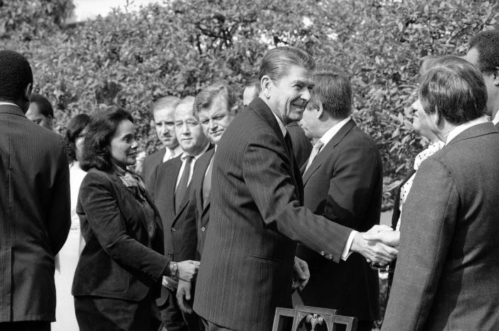 FILE - In this Nov. 2, 1983 file photo President Ronald Reagan, followed by Coretta Scott King, shakes hands with those in attendance to witness the signing of the bill making Martin Luther King, Jr.'s birthday a national holiday, in the Rose Garden. From left: King; Rep. Joe Biden, D-Del.; Sen. Charles McC. Mathias, R-Md.; Sen. Edward M. Kennedy, D-Mass.; Sen. Bob Dole, R-Kan.; Reagan; and Rep. Katie Hall, D-Ind. (AP Photo/Barry Thumma, File)