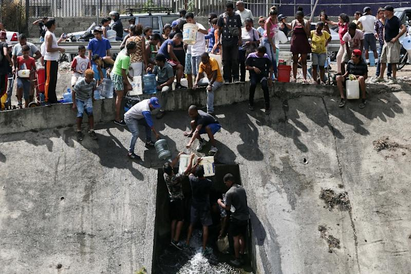 People collect water from a broken pipe flowing into a sewage canal at the Guaire river in Caracas on March 11, 2019 (AFP Photo/Cristian HERNANDEZ)