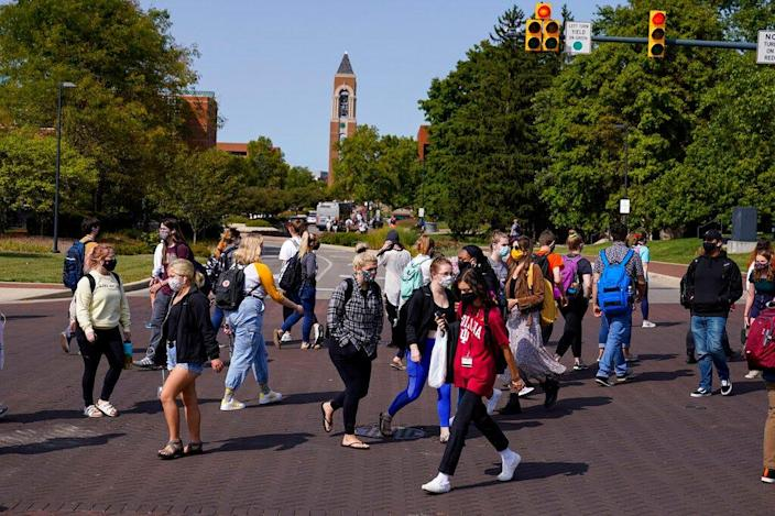 Masked students cross a cross on campus at Ball State University in Muncie, Ind., On September 10, 2020.