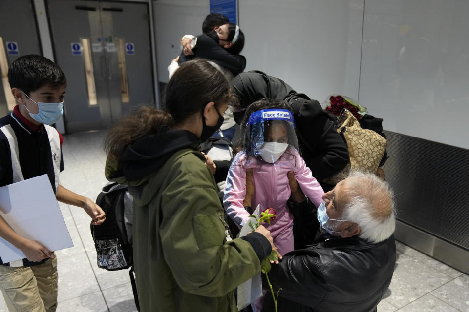 Members of the Mogul family are reunited as a grandfather embraces his granddaughter who arrived with her mother, top, on a flight from Charlotte, North Carolina, in the U.S. at Terminal 5 of Heathrow Airport in London, Monday, Aug. 2, 2021. Travelers fully vaccinated against coronavirus from the United States and much of Europe were able to enter Britain without quarantining starting today, a move welcomed by Britain's ailing travel industry. (AP Photo/Matt Dunham)