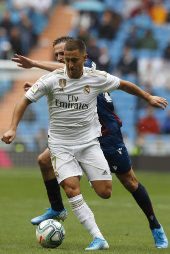 Real Madrid's Eden Hazard, front, vies for the ball with Levante's Jorge Miramon during the Spanish La Liga soccer match between Real Madrid and Levante at the Santiago Bernabeu stadium in Madrid, Spain, Saturday, Sept. 14, 2019. (AP Photo/Bernat Armangue)