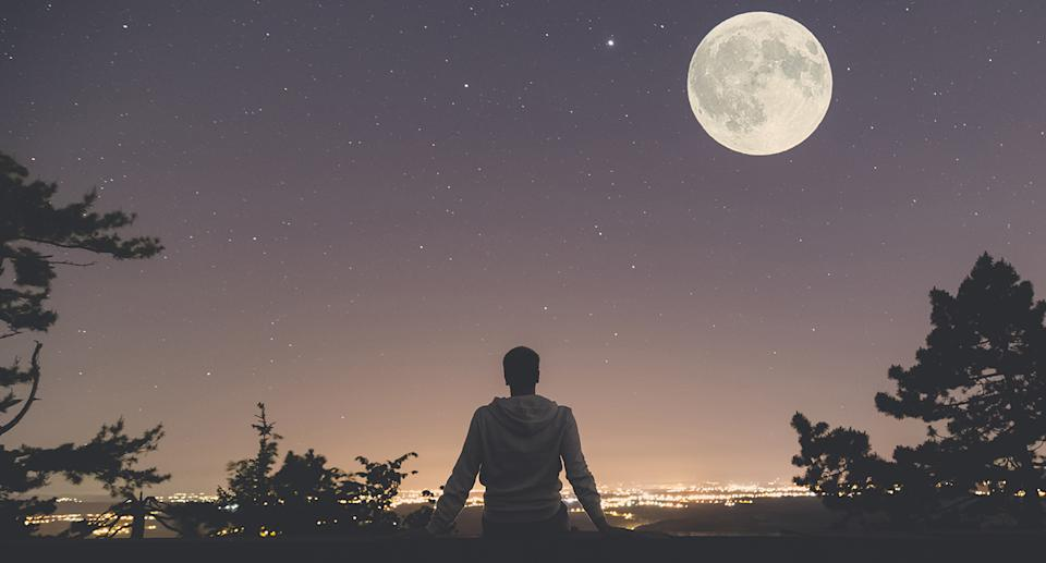 Photo shows a man sitting on a wall at night looking at the full moon.