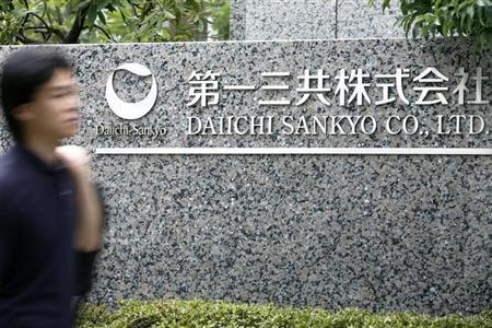 Man walks past a sign of Daiichi Sankyo Co., Ltd. at the company's head office in Tokyo