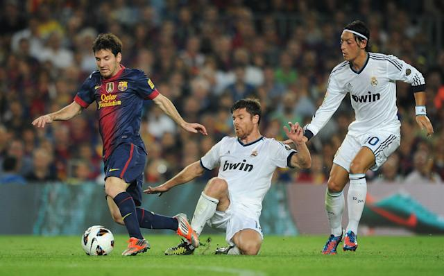 BARCELONA, SPAIN - OCTOBER 07: Lionel Messi (L) of Barcelona is fouled by Xabi Alonso (C) of Real Madrid as Mesut Ozil looks on during the la Liga match between FC Barcelona and Real Madrid at the Camp Nou stadium on October 7, 2012 in Barcelona, Spain. (Photo by Jasper Juinen/Getty Images)