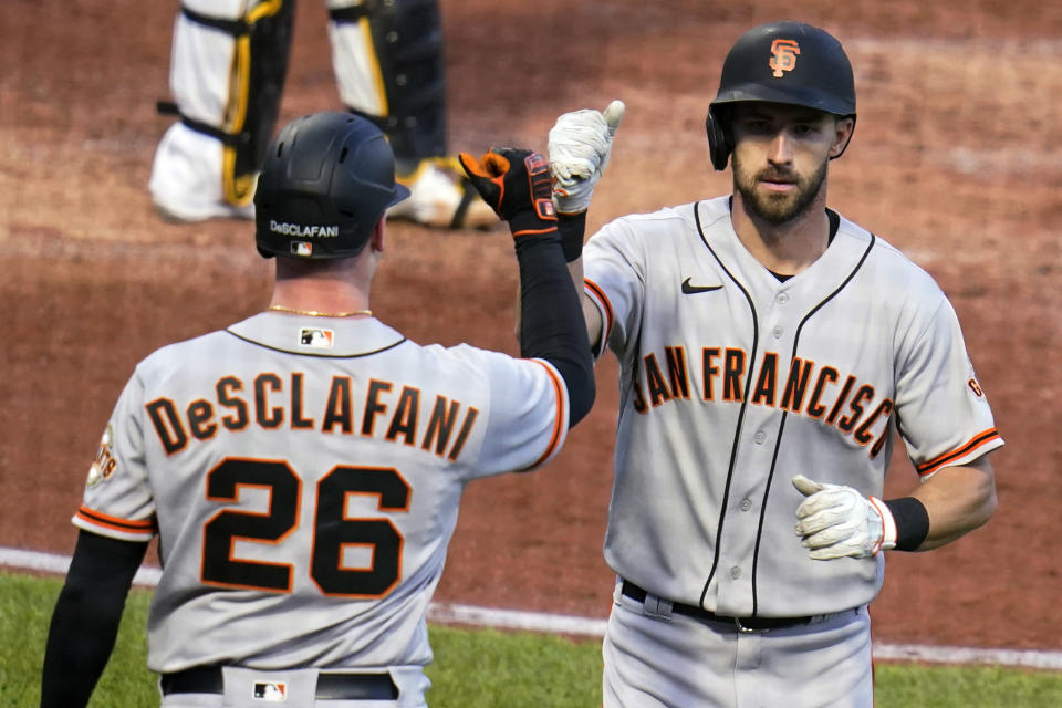 San Francisco Giants' Steven Duggar, right, is greeted by Anthony DeSclafani as he returns to the dugout after hitting a solo home run off Pittsburgh Pirates starting pitcher Wil Crowe during the fifth inning of a baseball game in Pittsburgh, Thursday, May 13, 2021.(AP Photo/Gene J. Puskar)