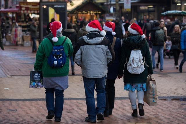 People in Santa hats doing last-minute Christmas shopping