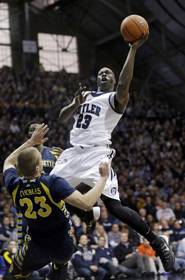 Marquette guard Jake Thomas, left, draws the charge from Butler forward Khyle Marshall in the first half of an NCAA college basketball game in Indianapolis, Saturday, Jan. 18, 2014. (AP Photo/Michael Conroy)