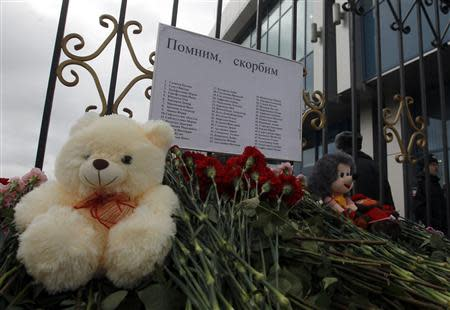 Flowers and stuffed toys are seen left near a fence of Kazan airport, under a sign giving names of victims of a Tatarstan Airlines Boeing 737 crash
