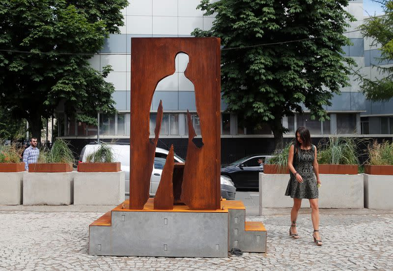 A woman walks past a monument honouring delivery couriers who continued to work throughout the outbreak of the coronavirus disease (COVID-19), in Moscow