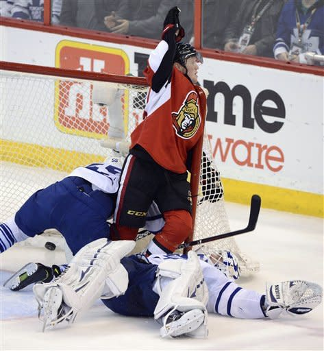 Ottawa Senators' Erik Condra, center, celebrates his goal as Toronto Maple Leafs goaltender Ben Scrivens, right, lies on his back and Korbinian Holzer falls into the net during the second period of an NHL hockey game in Ottawa, Ontario, on Saturday, Feb. 23, 2013. (AP Photo/The Canadian Press, Sean Kilpatrick)