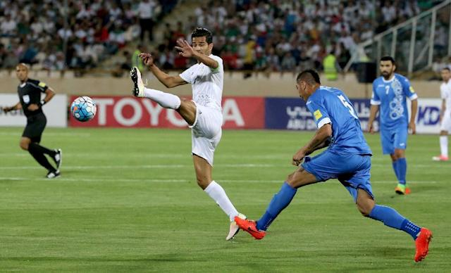 Iran's Masoud Shojaei (L) fights for the ball during a 2018 World Cup qualifying football match between Iran and Uzbekistan in Tehran on June 12, 2017 (AFP Photo/ATTA KENARE)