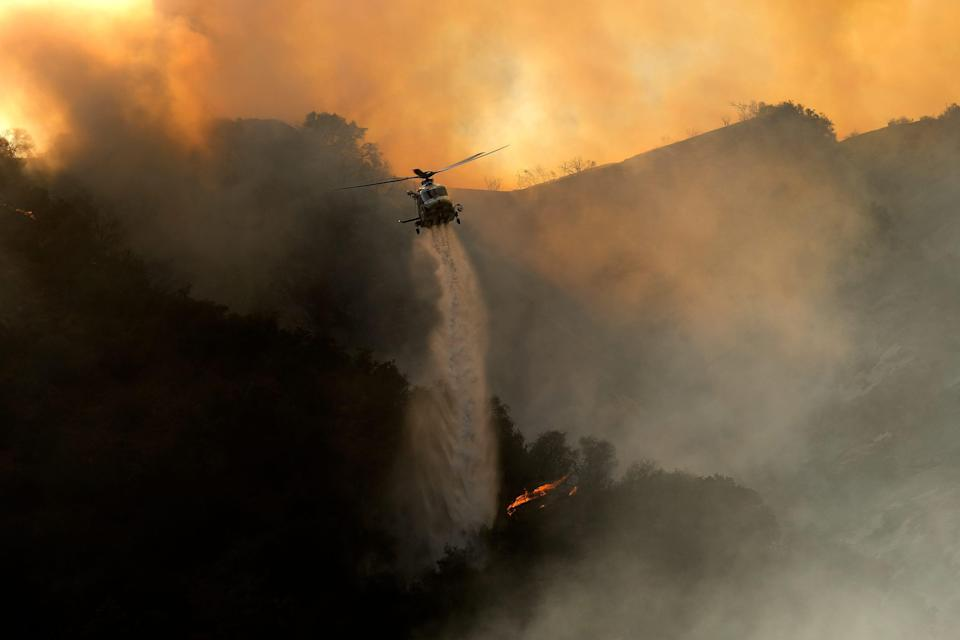 A firefighting helicopter drops water onto a brush fire in the Pacific Palisades area of Los Angeles on May 15, 2021.